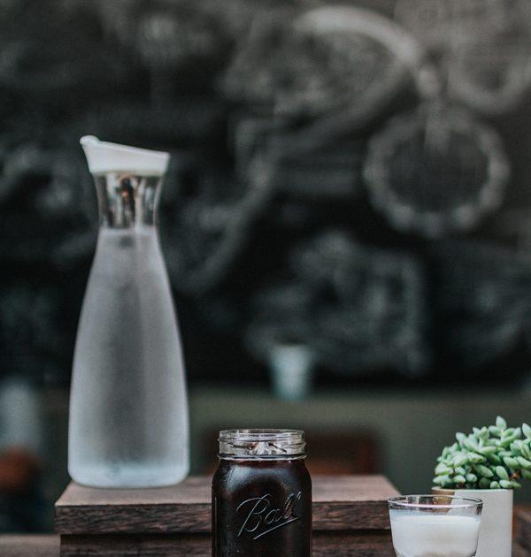 Cold Drip Kaffee Wasser und Milch stehen auf einem Holztisch