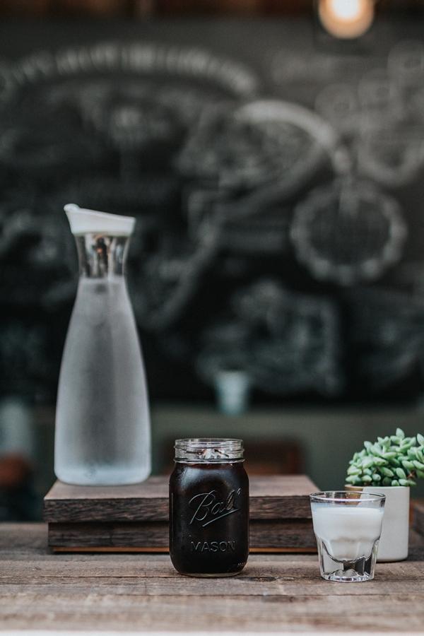 Kaffee Wasser und Milch stehen auf einem Holztisch
