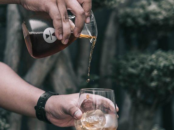 Im Cold Dripper gebrühter Cold Drip Kaffee wird von einer Glaskaraffe in ein Glas mit Eiswürfeln gegossen