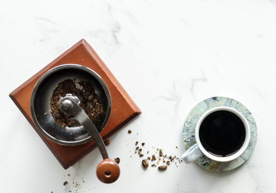 Kaffeemühle mit Kaffeetasse auf einem Tisch